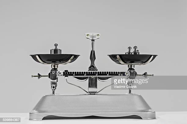 Old-fashioned weighing scale and weights against gray background