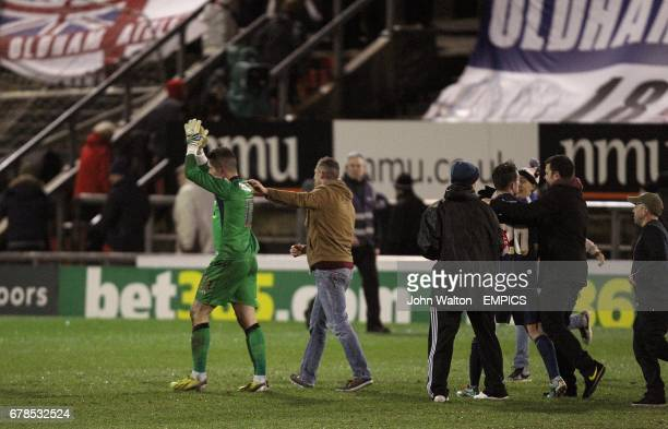 Oldham Athletic goalkeeper Dean Bouzanis is congratulated by fans who invade the pitch after their victory over Liverpool