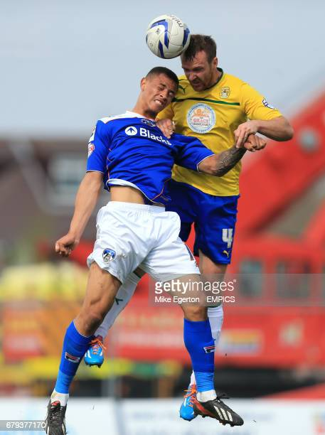 Oldham Athletic's Jonson Clarke Harris and Coventry City's Andy Webster battle for the ball in the air