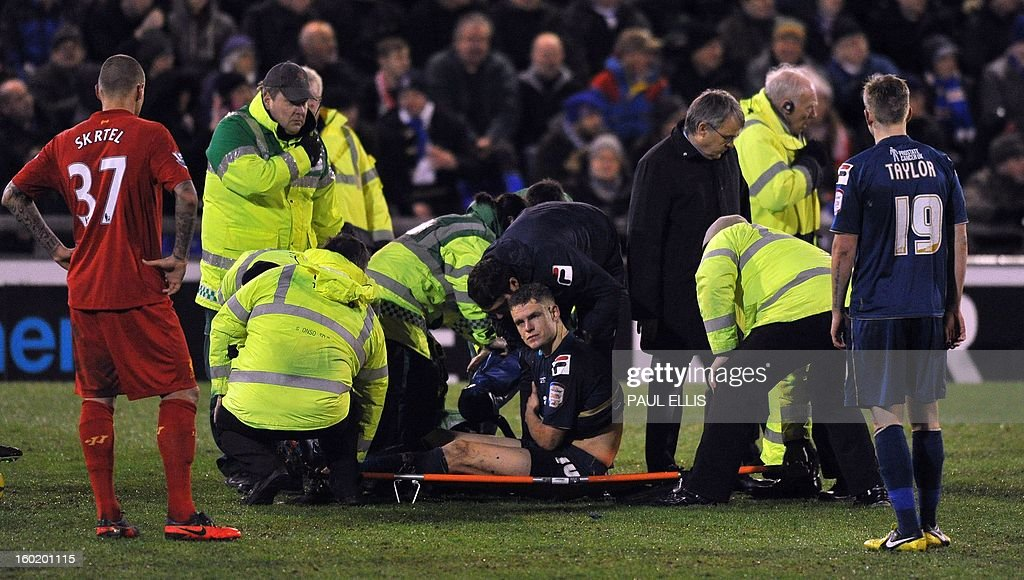 Oldham Athletic's Matt Smith (R) sits on a stretcher after being injured during the English FA Cup fourth round football match between Oldham Athletic and Liverpool at Boundary Park, Oldham, north-west England on January 27, 2013. English giants Liverpool were knocked out of the FA Cup after crashing 3-2 at third-division Oldham Athletic in the fourth round. AFP PHOTO/Paul Ellis - RESTRICTED