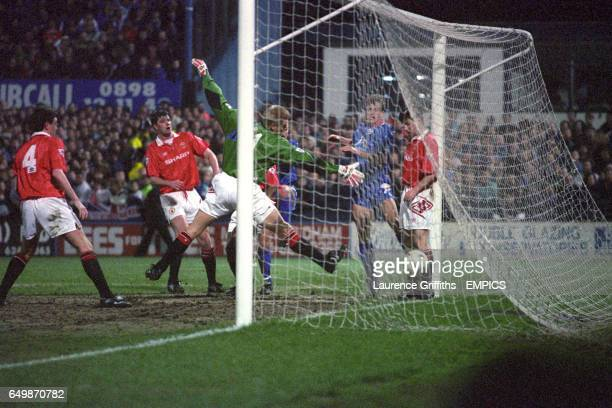 Oldham Athletic's Neil Adams scores past Manchester United goalkeeper Peter Schmeichel