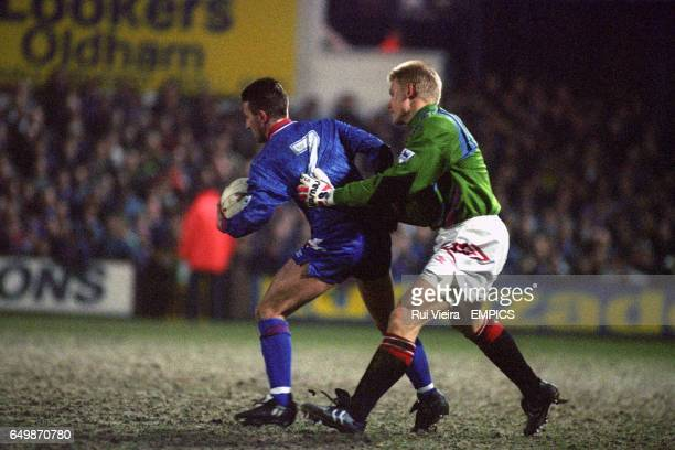 Oldham Athletic's Neil Adams tussles with Manchester United goalkeeper Peter Schmeichel