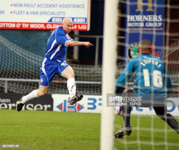 Oldham's Lee Hughes slots the ball past Brighton goal keeper Michel Kuipers to score the opening goal of the game
