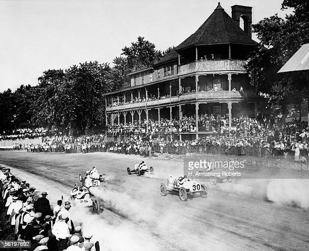 Oldtime Racetrack With Victorian Bleachers And Spectators Watching A Motor Car Race On The Dirt Speedway With Dust Plumes Following The OneMan...