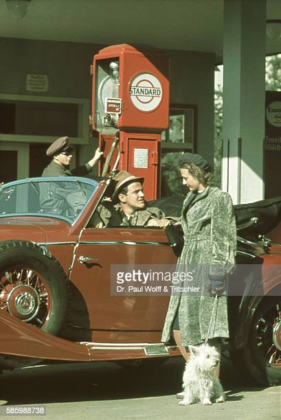Oldtimer at petrol station and attendant driver young woman with dog nostalgic