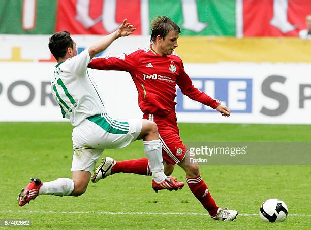 Oleg Kuzmin of FC Lokomotiv Moscow is challenged by Florentin Petre of FC Terek Grozny during the Russian Football League Championship match between...