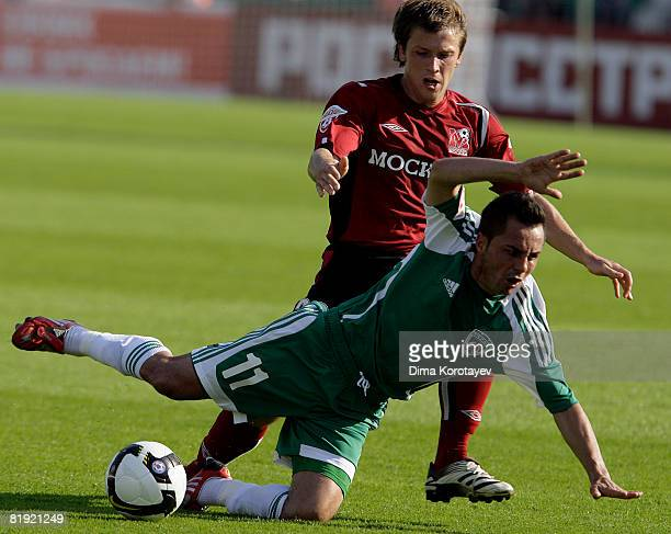Oleg Kuzmin of FC Moscow competes for the ball with Florentin Petre of FC Terek Grozny during the Russian Football League Championship match between...