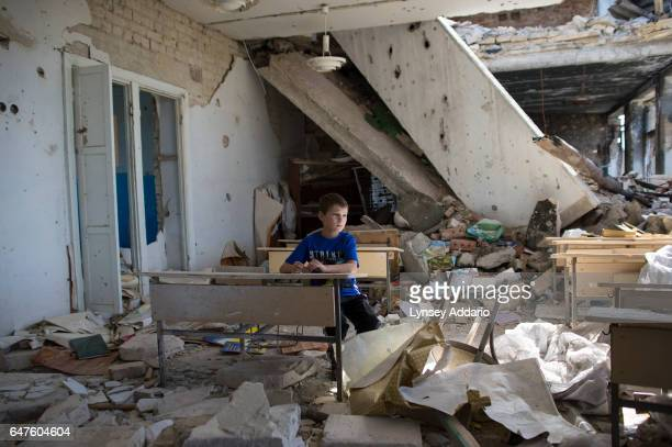 Oleg Teryokhin sits at a desk in one of the classrooms in his former school in Nikishino village which was destroyed by the east Ukraine war...