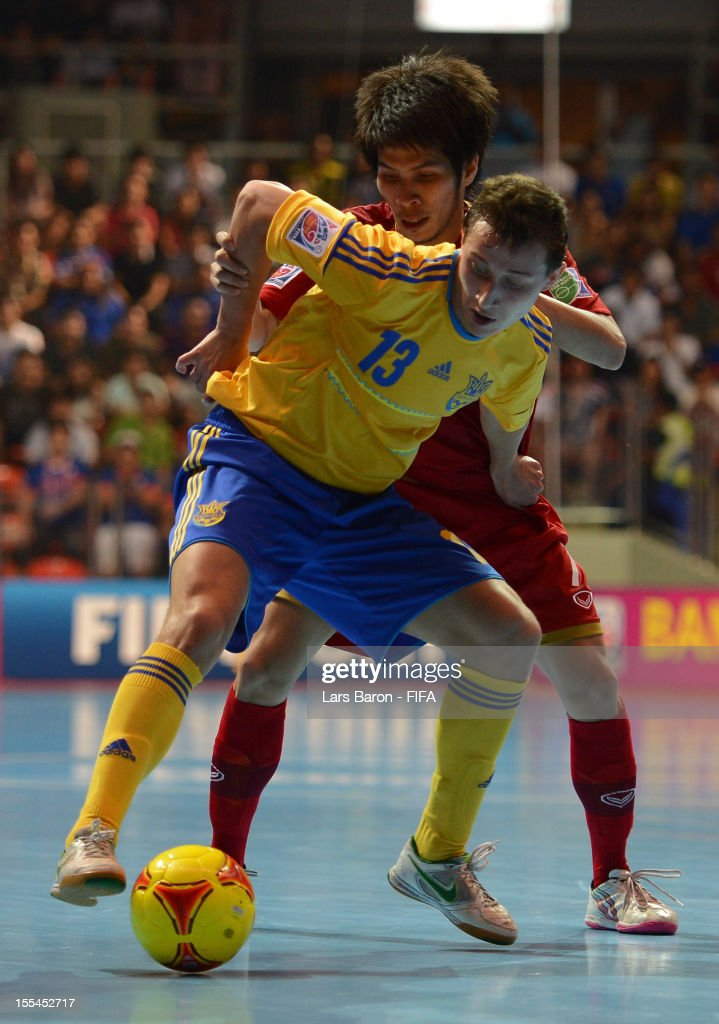 Oleksandr Sorokin of Ukraine is challenged by Kritsada Wongkaeo of Thailand during the FIFA Futsal World Cup Group A match between Thailand and Ukraine at Indoor Stadium Huamark on November 4, 2012 in Bangkok, Thailand.