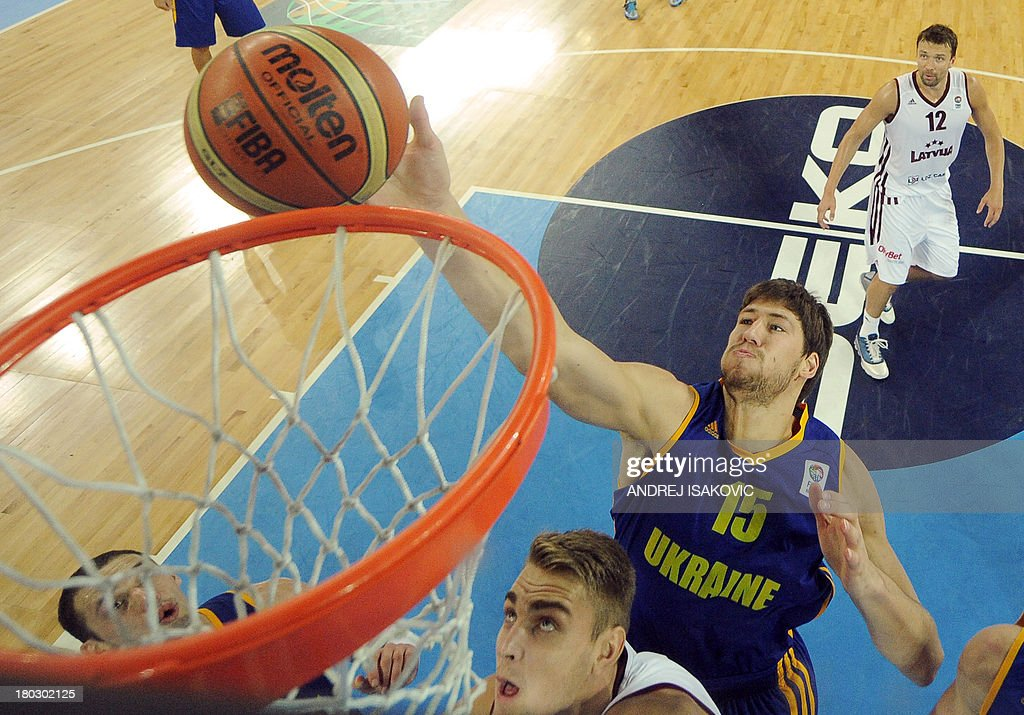 Olexandr Mishula of Ukraine (Bottom R) dunks the ball past Rolands Freimanis of Latvia during the FIBA EuroBasket second round Group E basketball championship qualification match between Latvia and Ukraine, in Ljubljana, Slovenia, on September 11, 2013.