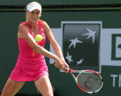 Olga Govortsova of Belarus hits a return to Petra Kvitova of the Czech Republic during day 3 of the BNP Paribas Open at Indian Wells Tennis Garden on...