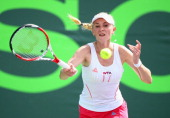 Olga Govortsova of Belarus returns a shot to Flavia Pennetta of Italy during their match on day 4 of the Sony Open at Crandon Park Tennis Center on...