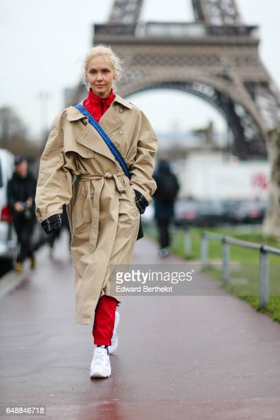 Olga Karput wears a beige trench coat a red turtleneck sweater red pants a bag with a blue strap and white sneakers shoes outside the Hermes show...