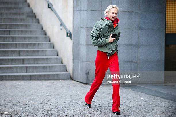 Olga Karput wears a green bomber jacket a red hoodie and red pants outside the Vetements show at Centre Pompidou during Paris Fashion Week Haute...