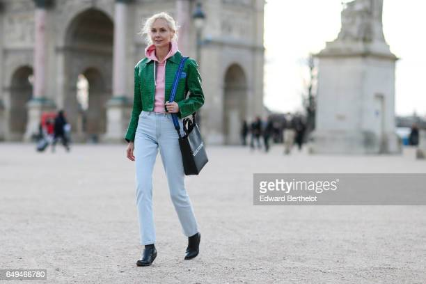 Olga Karput wears a pink hoodie sweater a green jacket jeans pants a black bag and black boots outside the Louis Vuitton show during Paris Fashion...