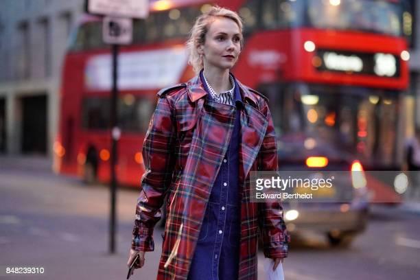 Olga Karput wears a red gingham plastic rain coat white heels and a blue denim dress outside the Burberry show during London Fashion Week September...