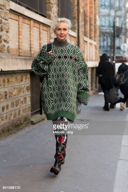 Olga Karput wears an oversized green patterned sweater and thighhigh leather boots with print outside the Lemaire show at Palais de la Femme on...
