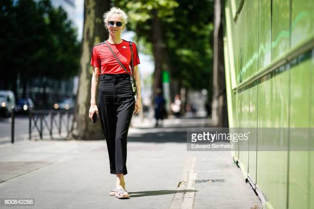 Olga Karput wears sunglasses a red top black pants sandals outside the Y3 show during Paris Fashion Week Menswear Spring/Summer 2018 on June 25 2017...