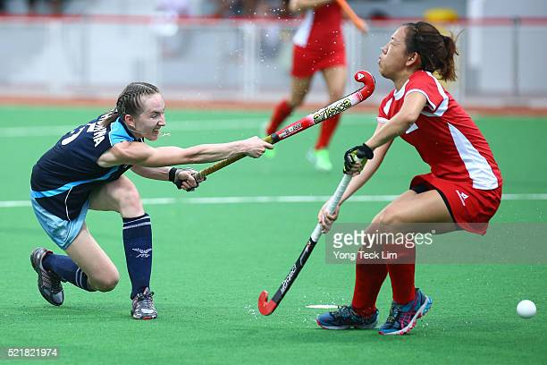 Olga Khonina of Kazakhstan takes a shot against Nicole Kwek of Singapore during round 1 of the 2016 Hockey World League at Sengkang Hockey Stadium on...