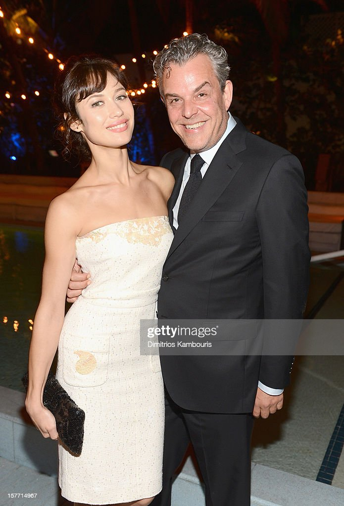 Olga Kurylenko (L) and actor Danny Huston attend a dinner and auction hosted by CHANEL to benefit the Henry Street Settlement at Soho Beach House on December 5, 2012 in Miami Beach, Florida.