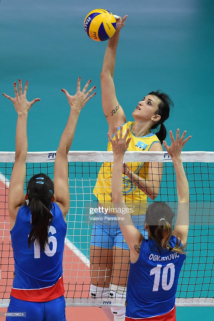 Olga Nassedkina of Kazakhstan spikes as <a gi-track='captionPersonalityLinkClicked' href=/galleries/search?phrase=Maja+Ognjenovic&family=editorial&specificpeople=3984599 ng-click='$event.stopPropagation()'>Maja Ognjenovic</a> (R) and Milena Rasic (L) of Serbia block during the FIVB Women's World Championship pool F match between Serbia and Kazakhstan on October 2, 2014 in Verona, .