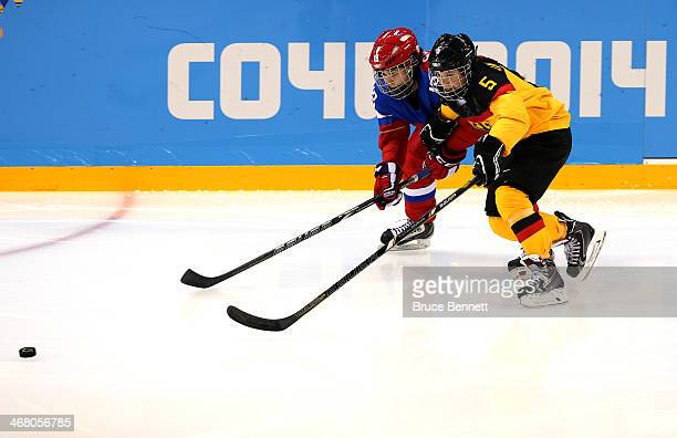 Olga Sosina of Russia skates for the puck against Manuela Anwander of Germany during the Women's Ice Hockey Preliminary Round Group B Game on day two...