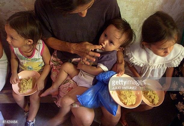 Olga Yanira is fed by her mother thanks to a program created to fight hunger in Orcuina Honduras 05 October 2002 Olga Yanira es alimentada por su...