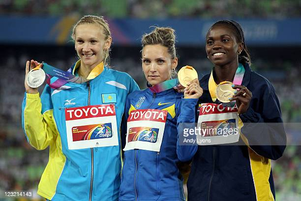Olha Saladuha of Ukraine poses with the gold medal Olga Rypakova of Kazakhstan the silver and Caterine Ibarguun of Colombia the bronze following the...