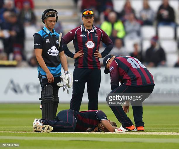 Oli Stone of Northamptonshire grimaces after appearing to hurt his leg whilst celebrating the wicket of Moeen Ali of Worcestershire during the...