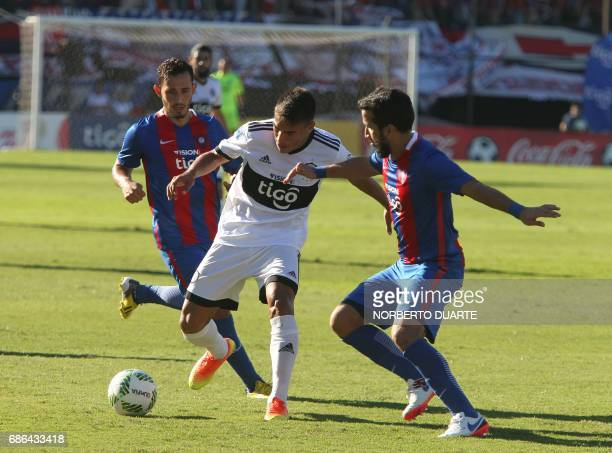 Olimpia's Aquilino Gimenez vies for the ball with Raul Caceres and Joel Gimenez of Cerro Porteno during their Paraguayan Apertura 2017 tournament...