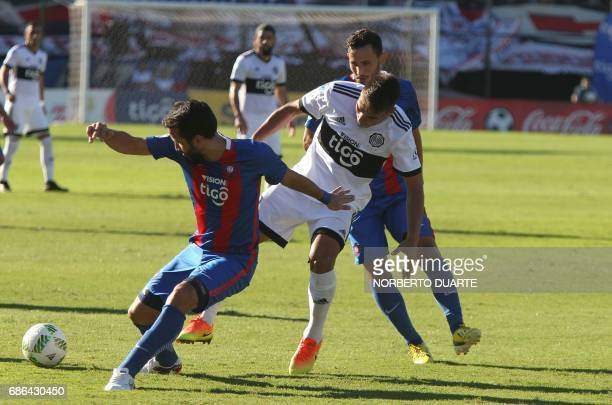 Olimpia's Aquilino Gimenez vies for the ball with Raul Caceress and Joel Gienez of Cerro Porteno during their Paraguayan Apertura 2017 tournament...