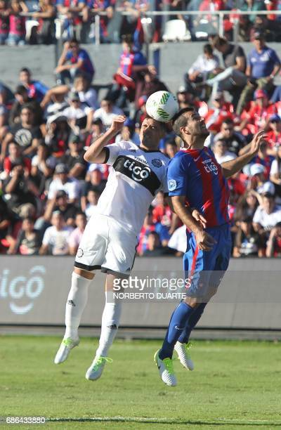 Olimpia's Julian Benitez vies for the ball with Santiago Molinas of Cerro Porteno during their Paraguayan Apertura 2017 tournament match at the...