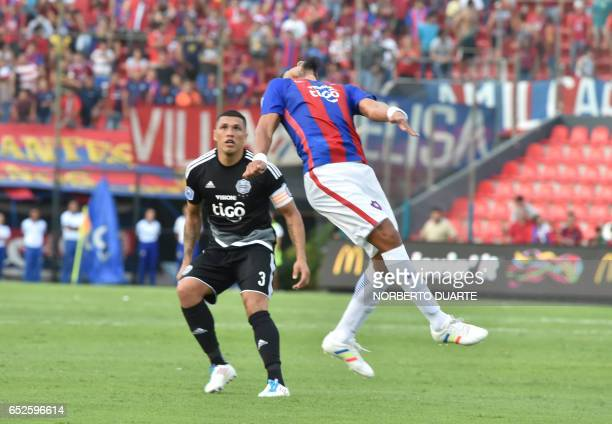 Olimpia's Richard Ortiz vies for the ball with Jorge Rojas of Cerro Porteno during their Paraguayan apertura 2017 tournament match at the Defensores...