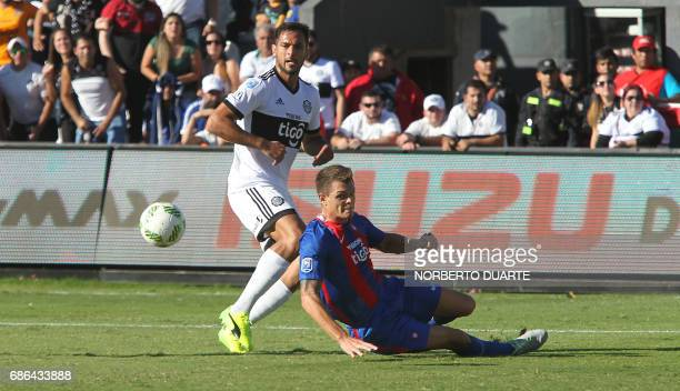 Olimpia's Roque Santa Crruz vies for the ball with Marcos Riveros of Cerro Porteno during their Paraguayan Apertura 2017 tournament match at the...