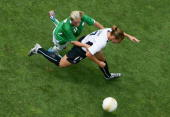 Oliva O'Toole of Team Ireland falls onto Lori Chalupny of Team USA as she drives with the ball during the international women's soccer game held on...