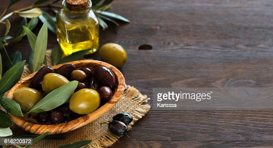 Olive oil and olives on wood background : Stock Photo