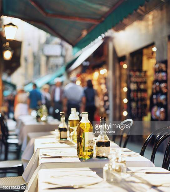 Olive oil and vinegar bottles on cafe table (focus on bottles)