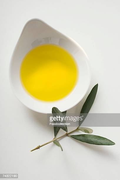 Olive oil in bowl, olive sprig beside it