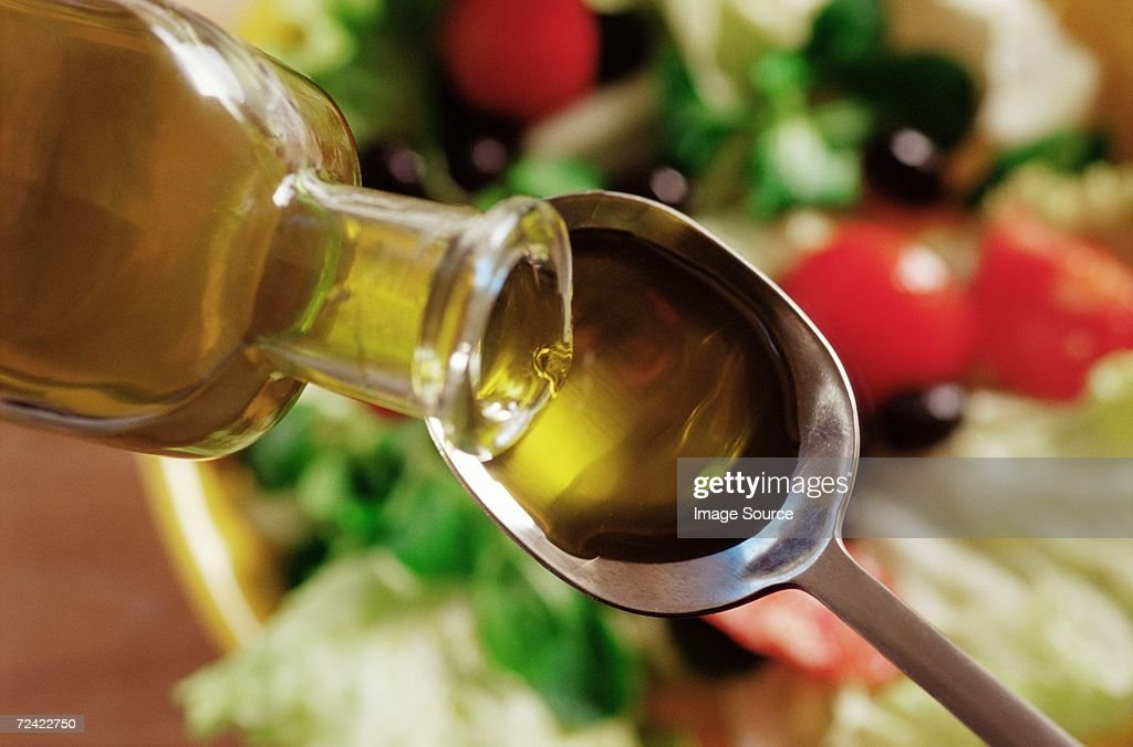Olive oil pouring on to a spoon : Stockfoto