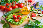 olive oil, cut tomato and fresh vegetables - healthy ingredients for cooking
