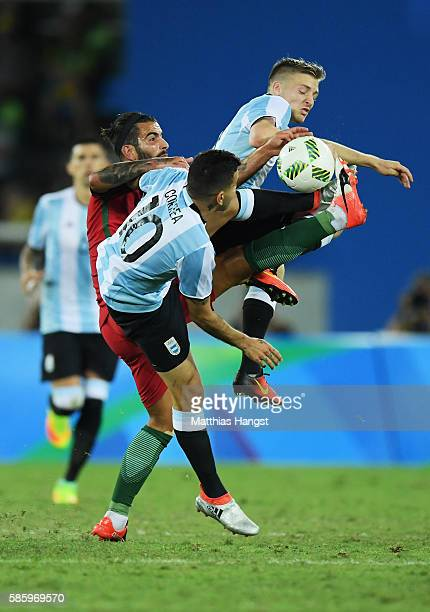 Oliveira Sergio of Portugal collides with Angel Correa and Victor Cuesta of Argentina during the Men's Group D first round match between Portugal and...
