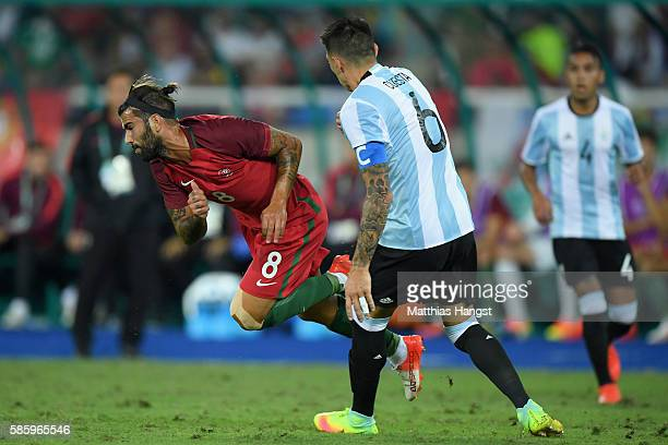 Oliveira Sergio of Portugal trips over Victor Cuesta of Argentina during the Men's Group D first round match between Portugal and Argentina during...