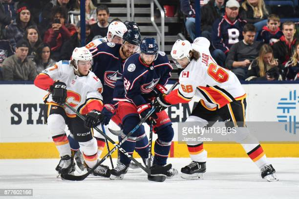 Oliver Bjorkstrand of the Columbus Blue Jackets battle for the puck with Mark Jankowski and Jaromir Jagr of the Calgary Flames during the first...