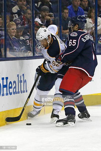Oliver Bjorkstrand of the Columbus Blue Jackets checks Alexander Sulzer of the Buffalo Sabres while battling for control of the puck on September...
