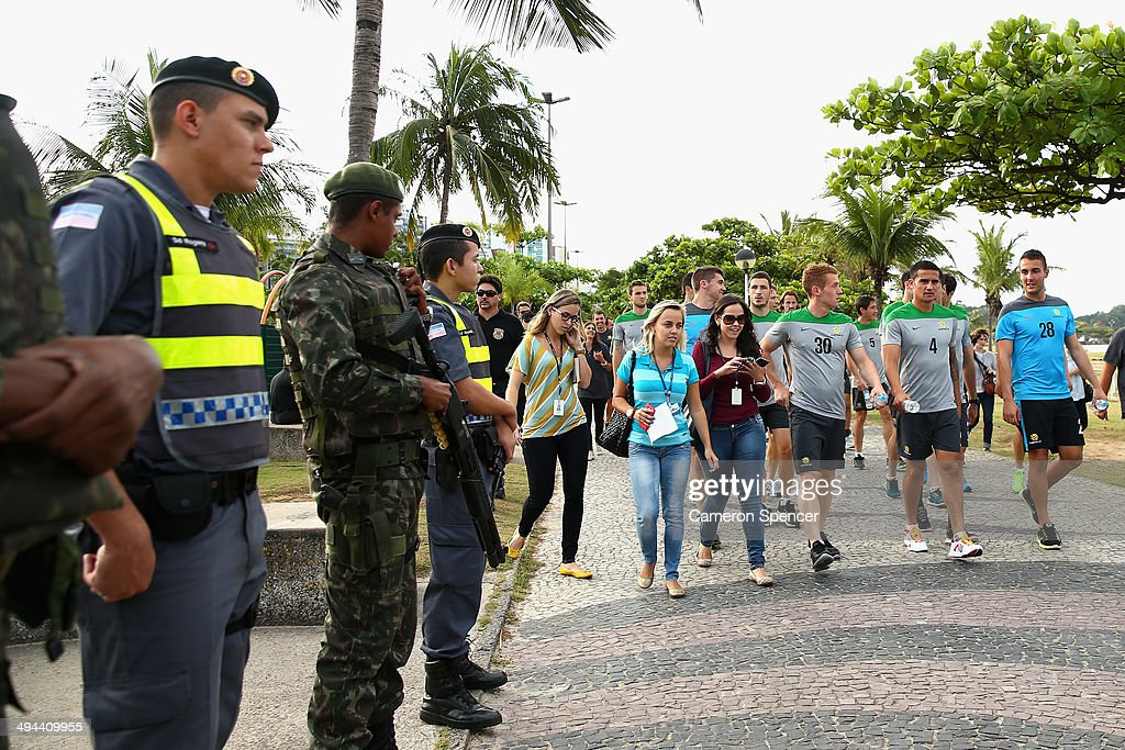 Oliver Bozanic, Tim Cahill and Mark Birighitti walk past police and army personnel during a beach walk at Praca dos Desejos on May 29, 2014 in Vitoria, Brazil. The Socceroos will compete in the 2014 FIFA World Cup, which begins on June 12.