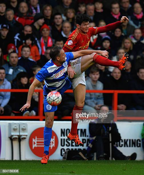 Oliver Burke of Nottingham Forest is tackled by Clint Hill of Queens Park Rangers during The Emirates FA Cup Third Round match between Nottingham...