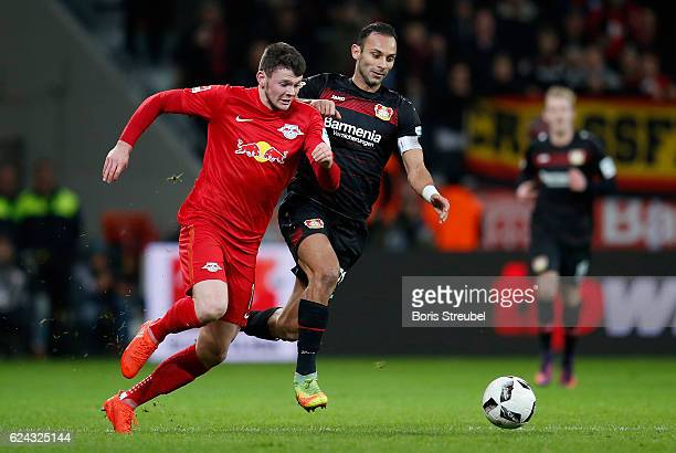 Oliver Burke of RB Leipzig is challenged by Oemer Toprak of Bayer 04 Leverkusen during the Bundesliga match between Bayer 04 Leverkusen and RB...