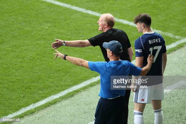 Oliver Burke of West Bromwich Albion with Gary Megson and Tony Pulis the head coach / manager of West Bromwich Albion before making his debut during...