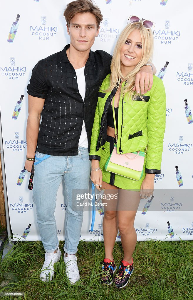 Oliver Cheshire (L) and Pixie Lott attend the Mahiki Rum Bar for the launch of the Mahiki Rum Family backstage during day 1 of the V Festival 2014 at Hylands Park on August 16, 2014 in Chelmsford, England.