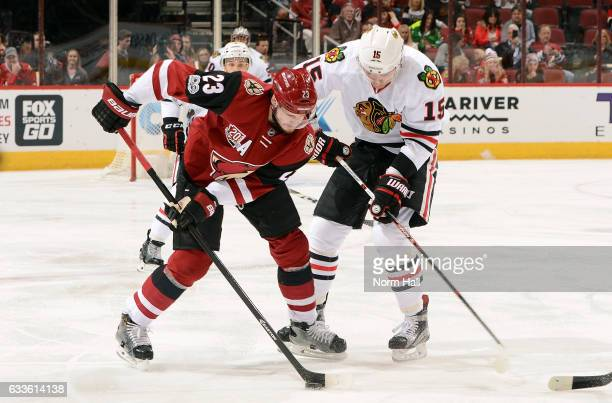 Oliver EkmanLarsson of the Arizona Coyotes and Artem Anisimov the Chicago Blackhawks battle for the puck during the first period at Gila River Arena...
